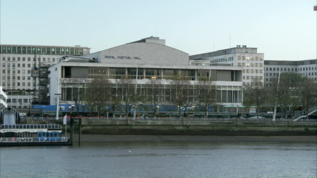 the river thames flows past the royal festival hall. available in hd. - royal festival hall stock videos & royalty-free footage