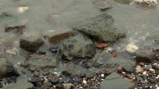 the river thames washes over rocks and pebbles. - flussufer stock-videos und b-roll-filmmaterial