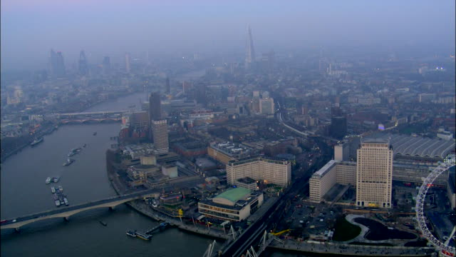 the river thames winds around waterloo station, the london eye and london town. - fog stock videos & royalty-free footage