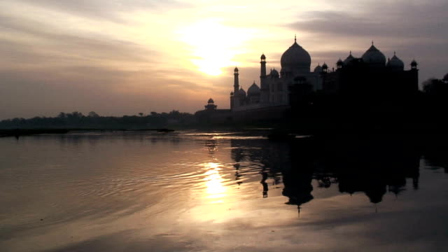 The River Yamuna reflects the Taj Mahal during the golden hour in Agra, India.