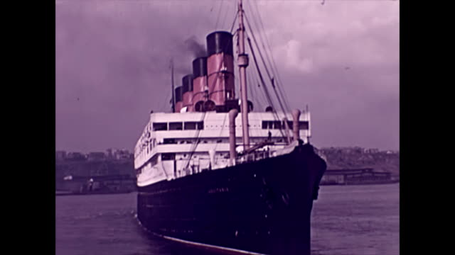 the rms aquitania reverses away from the dock on the hudson river in new york city / tugs attend the ship as she maneuvers for departure - passagierschiff stock-videos und b-roll-filmmaterial