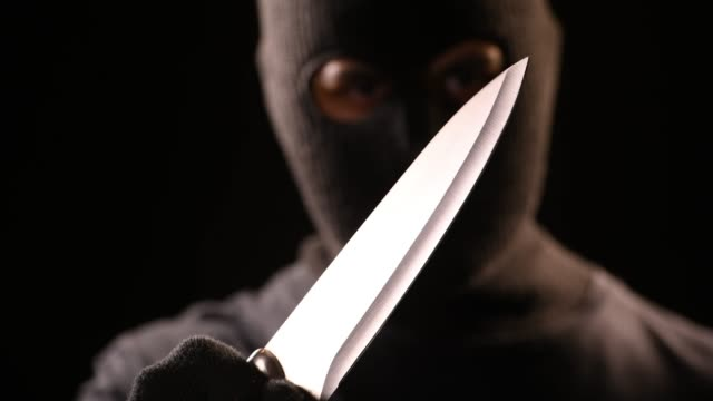 The robber hold the knife in hand