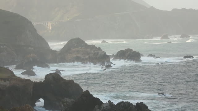 The rocky coast line of Big Sur with waves crashing on to the shore and sun shining.