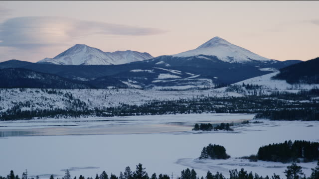 the rocky mountains at dusk over frozen dillon reservoir in winter with vehicles speeding along interstate 70 in the foreground in sunset - frozen stock videos & royalty-free footage
