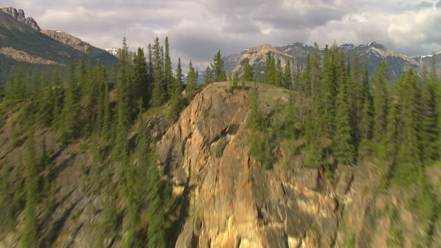 the rocky mountains surround a forest valley. - mountain stock videos & royalty-free footage