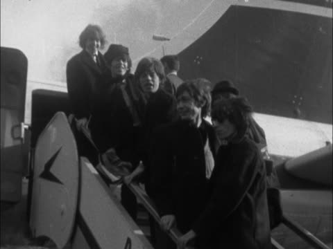vídeos de stock e filmes b-roll de the rolling stones get off airport bus, board plane, posing on stairs as other passengers pass by. - rolling stones
