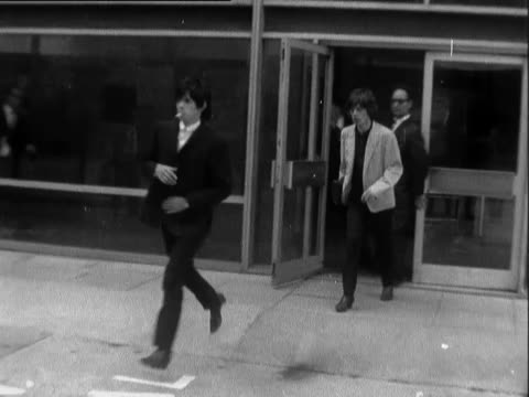 vídeos de stock e filmes b-roll de the rolling stones return from the usa and are met by fans at the airport / rolling stones along tarmac fans follow police help rolling stones... - 1964