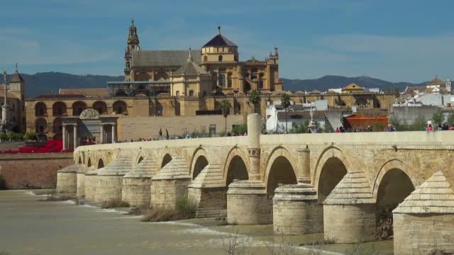 the roman bridge and the mosque cathedral of cordoba - bro bildbanksvideor och videomaterial från bakom kulisserna
