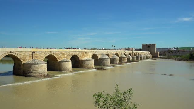 the roman bridge over the river at cordoba - arco architettura video stock e b–roll