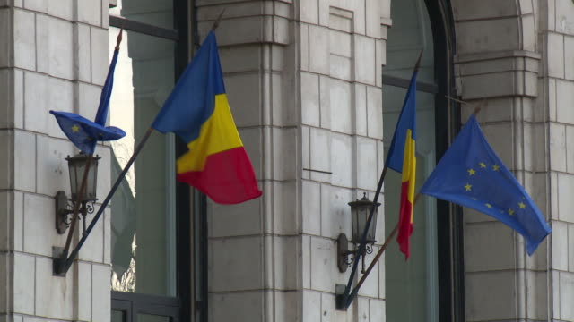 The Romanian and European Union flags hang outside the Palace of the Parliament in Bucharest, Romania.