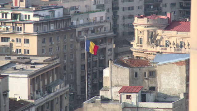 The Romanian flag, seen through heat haze from smoke, flies above rooftops in Bucharest, Romania.