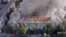 The roof of a residential house is burning. firefighters extinguish a fire on the roof of a residential high-rise building.