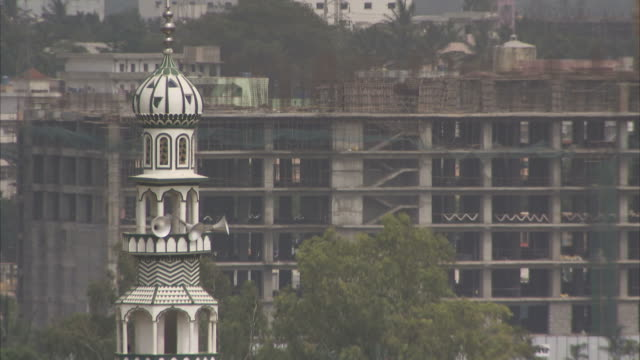 the rooftop of a building under construction sits behind a nearby tower. - bangalore stock videos and b-roll footage