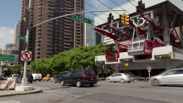 vidéos et rushes de the roosevelt island tram departs the station in manhattan.  the aerial tramway spans the east river from roosevelt island to manhattan.  the camera pans as it departs and traffic from 2nd avenue zooms by below - ligne de tramway