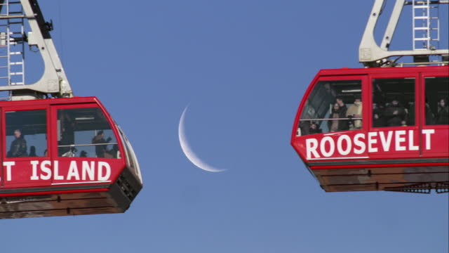 the roosevelt island trams pass each other on crossing the east river.  the moon is behind. - straßenbahnstrecke stock-videos und b-roll-filmmaterial