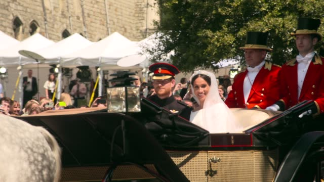 the royal couple ride out of windsor castle in an open top carriage after at the royal wedding 2018 prince harry and ms meghan markle on may 19 2018... - königliche hochzeit stock-videos und b-roll-filmmaterial