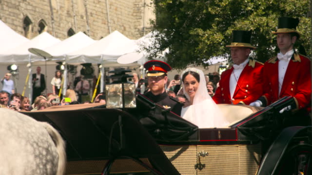 vídeos de stock e filmes b-roll de the royal couple ride out of windsor castle in an open top carriage after at the royal wedding 2018 prince harry and ms meghan markle on may 19, 2018... - casamento