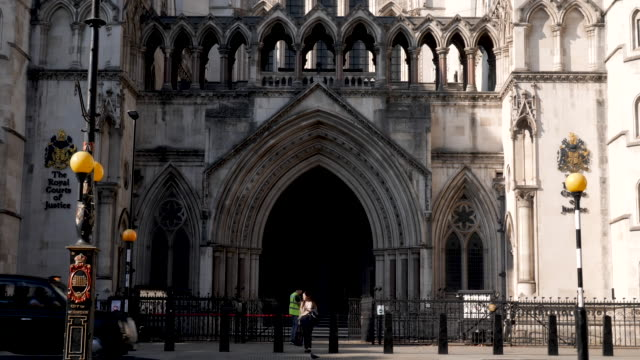 the royal courts of justice in london, england, uk. entrance shot with black taxi cabs passing by on the street. - law stock videos & royalty-free footage