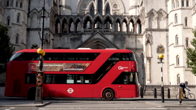 the royal courts of justice in london, england, uk. front entrance. red bus slows to let cyclist join the road and ride off. the cyclists thanks the bus driver. - justice concept stock videos & royalty-free footage