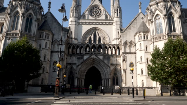 the royal courts of justice in london, england, uk. front entrance view, quiet day with very few people of traffic due to the coronavirus lockdown - justice concept stock videos & royalty-free footage