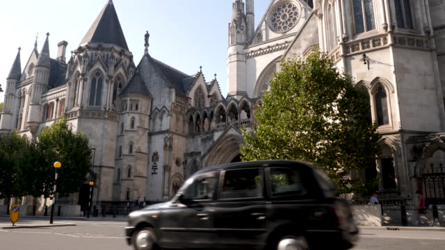 the royal courts of justice in london, england, uk. side angle showing taxi and people passing by. - justice concept stock videos & royalty-free footage