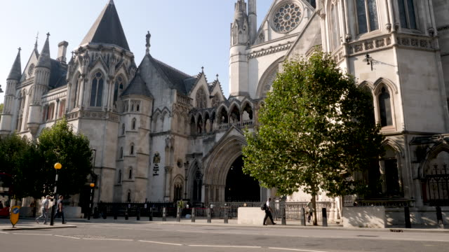 the royal courts of justice in london, england, uk. side view, quiet day with very few people or traffic due to the coronavirus lockdown - column stock videos & royalty-free footage