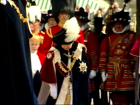 The Royal Family dressed in blue velvet robes walk in procession to St George's Chapel Windsor