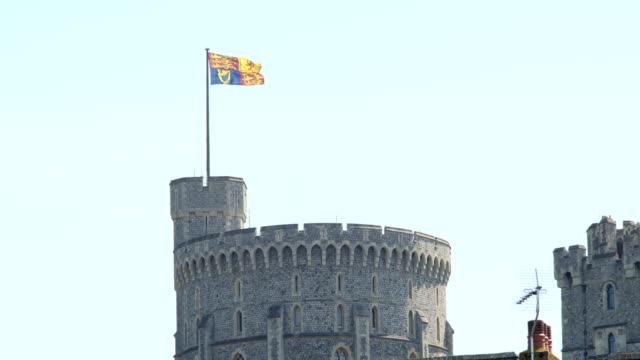 the royal standard flag flies high above the round tower of windsor castle on the queen's 94th birthday filmed on april 21, 2020 in london, england.... - ウィンザー城点の映像素材/bロール