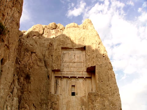the ruins at naqsh-e rustam are nestled in the side of a cliff. - persepoli video stock e b–roll
