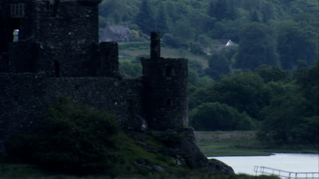 the ruins of kilchurn castle loom over loch awe. available in hd. - kilchurn castle stock videos and b-roll footage
