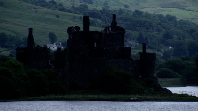 vídeos de stock, filmes e b-roll de the ruins of kilchurn castle loom over loch awe. available in hd. - loch