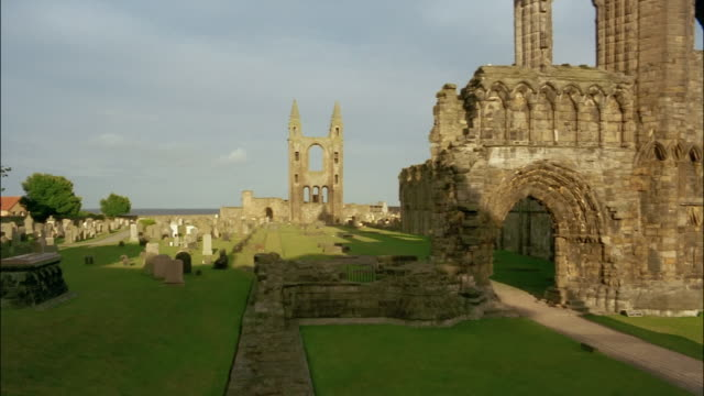 the ruins of st. andrews cathedral tower over a surrounding lawn. - st. andrews scotland stock videos & royalty-free footage