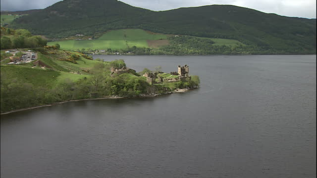 vídeos de stock, filmes e b-roll de the ruins of urquhart castle perches on the shore of loch ness in scotland. - escócia