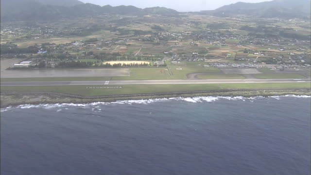 The runway of the Tokunoshima Airport follows the coast of Tokunoshima Island, Japan.