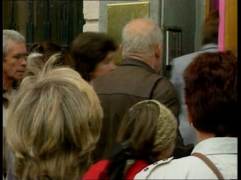 The Russian economic crisis deepens ITN Moscow EXT Crowd of people queuing outside bank GBV Female employees jostling at front of queue to get into...