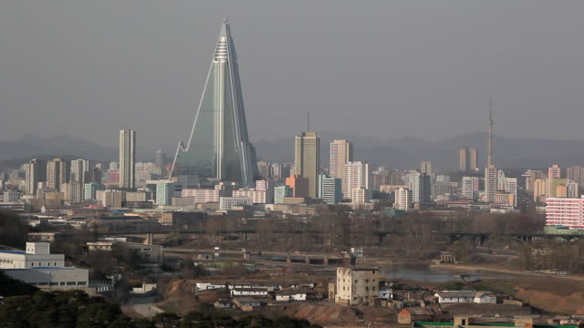 the ryugyong hotel towers over the surrounding buildings in pyongyang. - pyongyang stock videos and b-roll footage