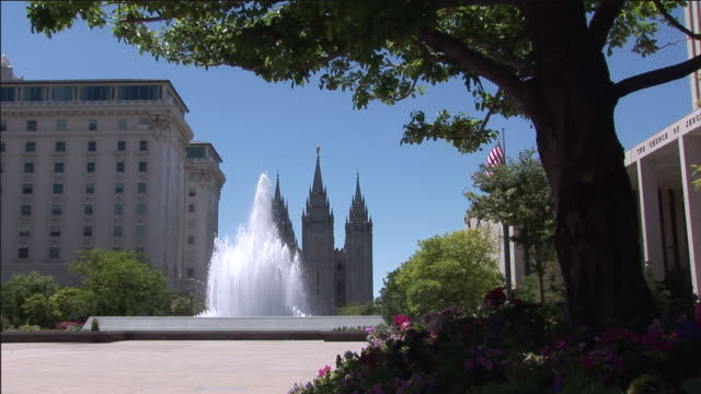the salt lake temple overlooks a fountain on temple square. - mormonism stock videos & royalty-free footage
