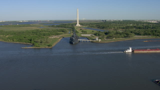 the san jacinto monument towers in the center of the houston ship channel. - battleship stock videos & royalty-free footage