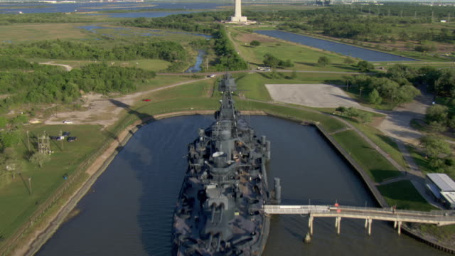 the san jacinto monument towers in the center of the houston ship channel. - schlachtschiff stock-videos und b-roll-filmmaterial