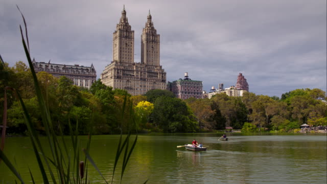 the san remo building overlooking people paddle boating in the central park lake - remo stock videos and b-roll footage