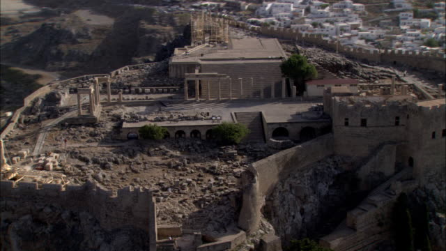 the sanctuary of athena atop an acropolis overlooks the island of lindos. - insel rhodos inselgruppe dodekanes stock-videos und b-roll-filmmaterial