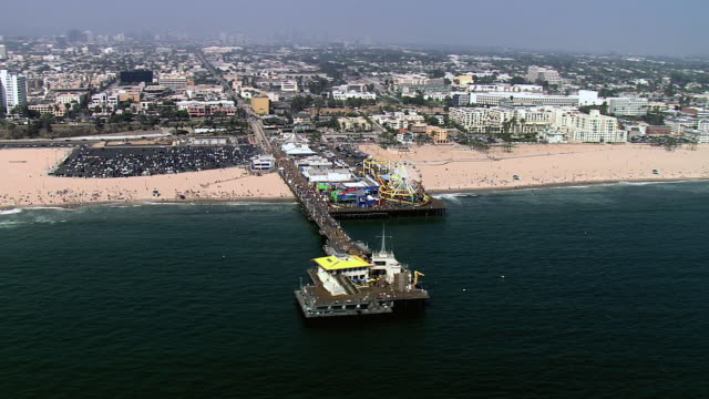 AERIAL The Santa Monica Pier under blue skies with the city in the background / Santa Monica, California, United States of America