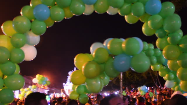the 'sapos' district 'conga' starts playing music amid a crowd of people. they have green balloons and their float can be seen in the distance. the... - 社会史点の映像素材/bロール
