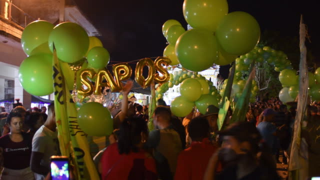 the 'sapos' district supporters start organizing with green balloons to dance in the street to the beat of a 'conga' music. they hold green balloons... - unesco organised group stock videos & royalty-free footage