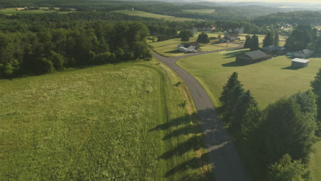 the scenery aerial view of poconos, monroe county, pennsylvania. the sunny summer morning. the panoramic overview over the field and forest to the kunkletown, then to the small farm near by the road. - pennsylvania stock videos & royalty-free footage