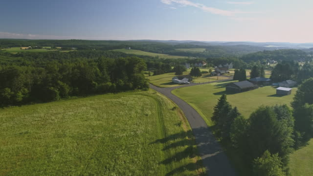 The scenery aerial view of Poconos, Monroe County, Pennsylvania. The sunny summer morning. The panoramic overview over the field and forest to the Kunkletown, then to the small farm near by the road.