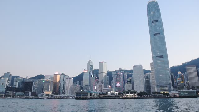 stockvideo's en b-roll-footage met the scenery of the victoria harbour with hong kong skyline against the clear blue sky.- wide rolling - hong kong