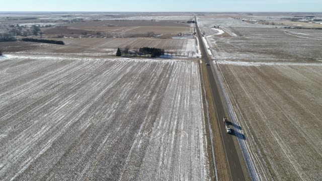 the scenic panoramic aerial video of the heavy truck driving on the small highway between the harvested fields in the country farmland - kansas stock videos & royalty-free footage