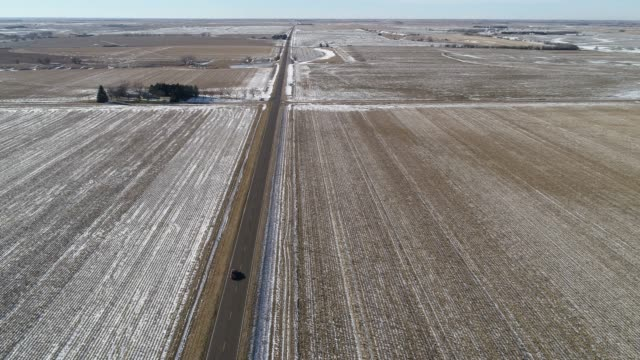 the scenic panoramic aerial view of the car driving on the small highway between the harvested fields in the country farmland - nebraska stock videos & royalty-free footage