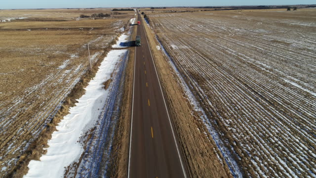 the scenic panoramic aerial view of the car driving on the small highway between the harvested fields in the country farmland - kansas stock videos & royalty-free footage